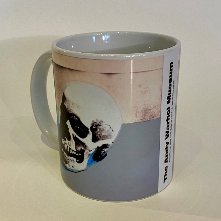 """A white mug with a Warhol """"Skull"""" artwork in gray and tans, and the words """"The Andy Warhol Museum"""" running vertically opposite the handle."""