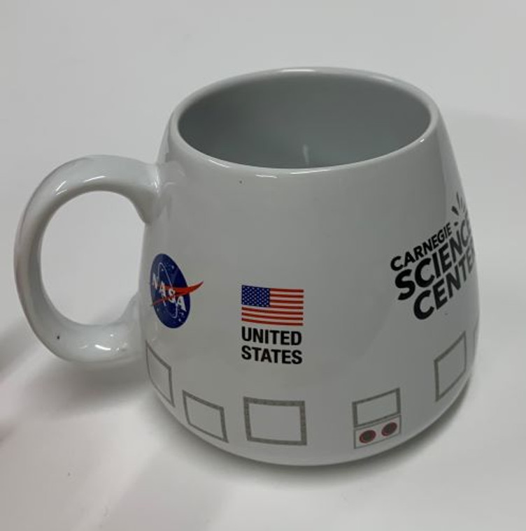 This image shows a white mug with a space capsule shape.  It has a NASA logo, Carnegie Science Center logo and the US Flag along with other capsule details.