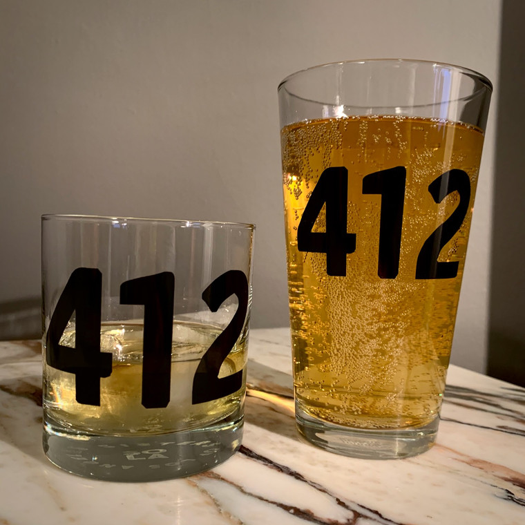 """Two glasses, one short and one tall and with """"412"""" on both of them, sitting on marble counter."""