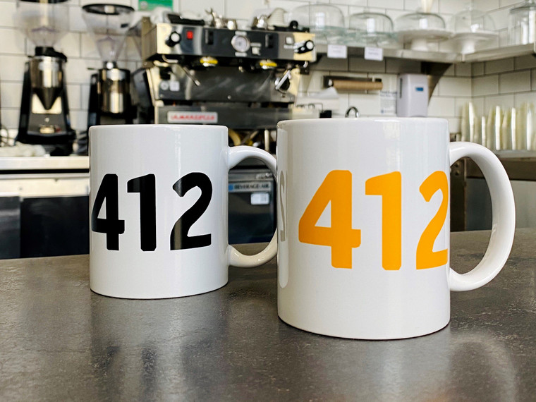"""Two white mugs with """"412"""" on them, sitting on a café counter."""