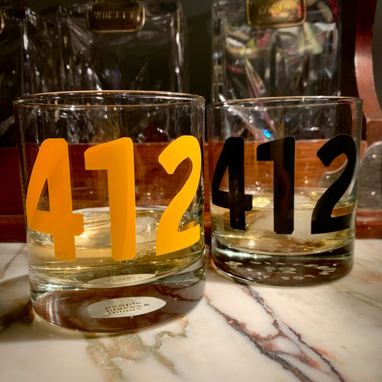 "Two short glasses with ""412"" sitting on a marble counter."