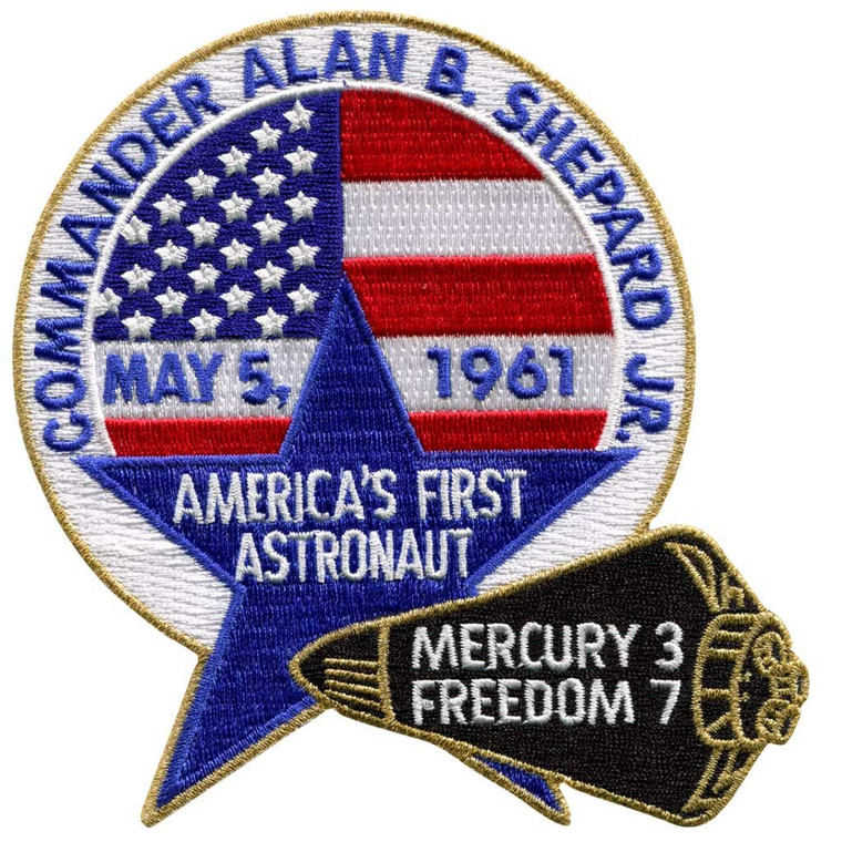 This image shows a patch with Commander Alan Shepard around the top of the circle.   It has May 5, 1961 as the date on it, and says he is America's first astronaut.