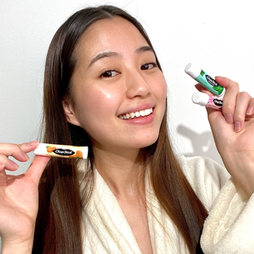Young woman holding ChapStick® Spa Collection three pack.