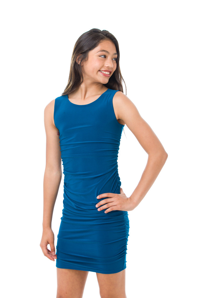 A close up view of the Tween Girls Teal Ruched Fitted Dress in Longer Length side view. A perfect dress with all over stretch.