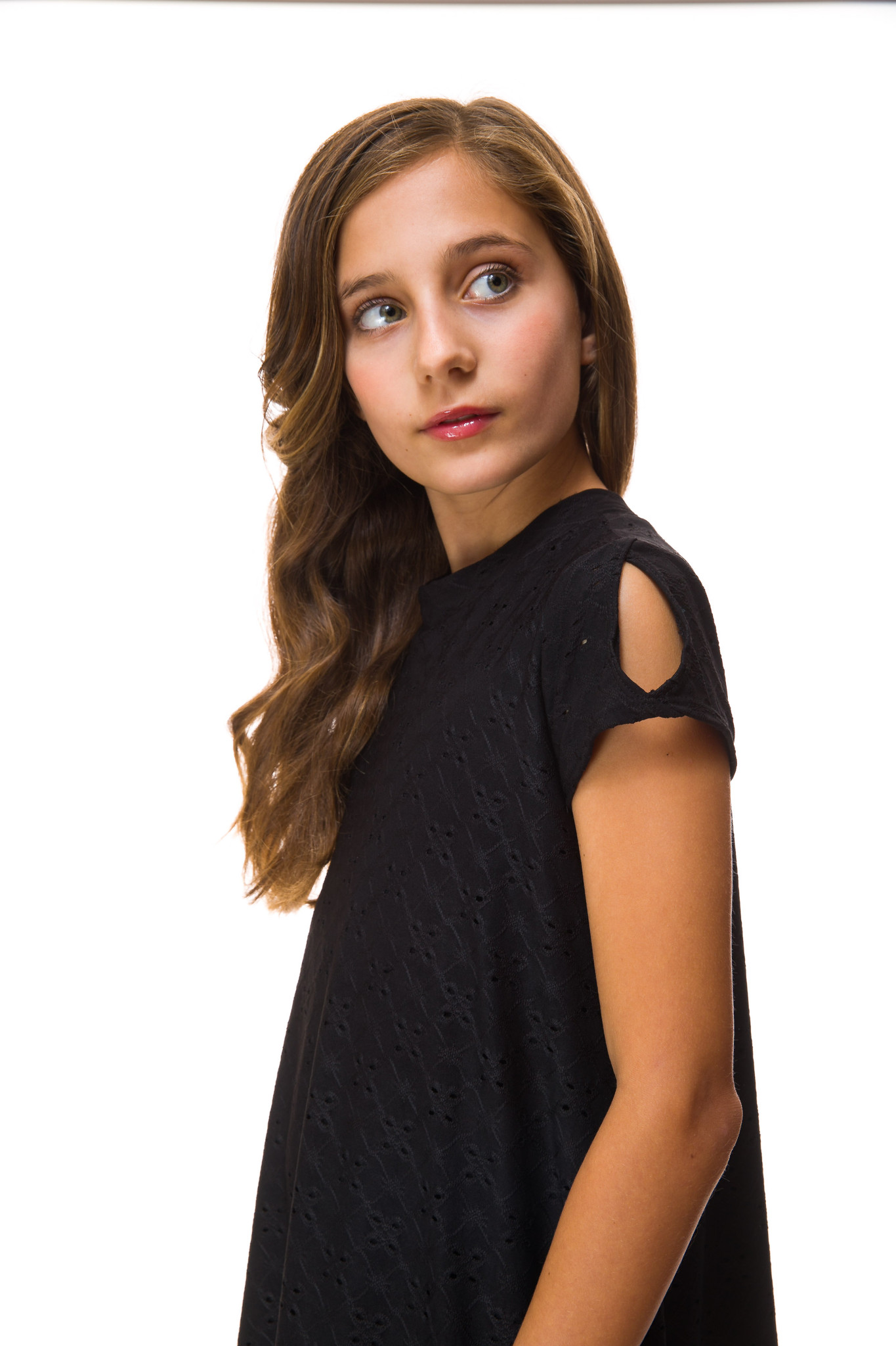 A side shoulder view of the Tween Girls Cold Shoulder A Line Dress in Black Eyelet.