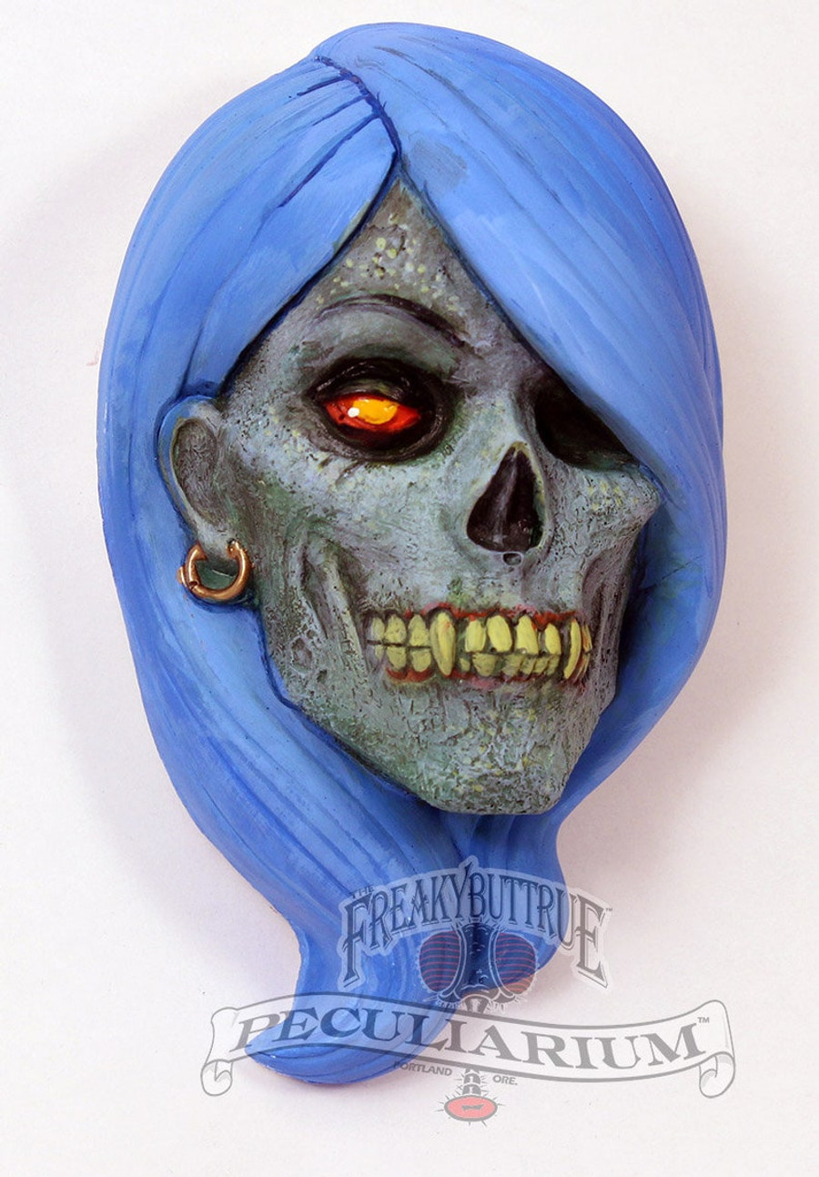 This is a brand new sculpt of a lovely zombie vampire woman, she's got it going on! It's stone cast from an original sculpt by master sculptor Colin Batty and each is individually hand painted. Also available in faux bronze, also hand done. Thus, each one is a little different. It's about 4 inches from the top to bottom. PLEASE INDICATE HAIR COLOR! Get yours today!