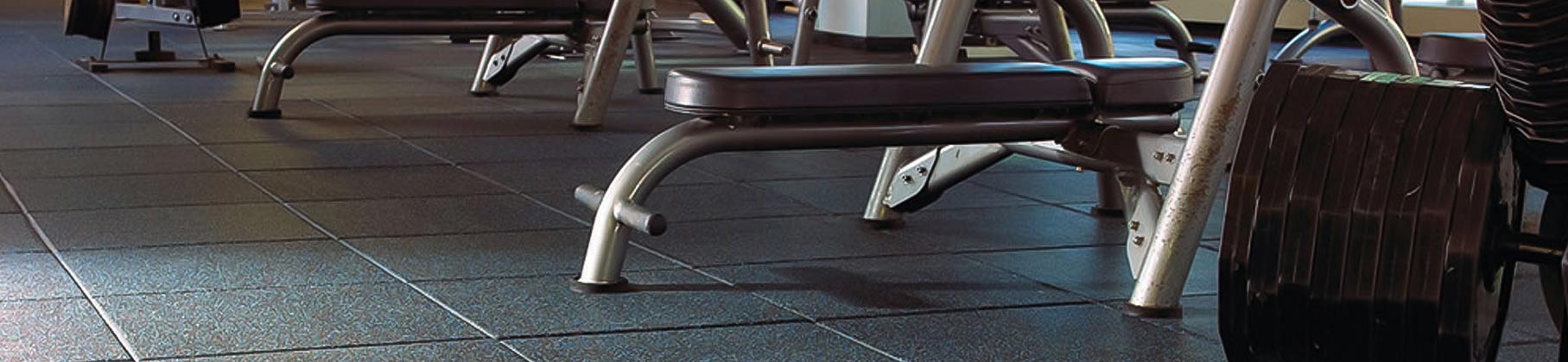 Bench presses on top of rubber flooring tiles for gyms from Zogics.