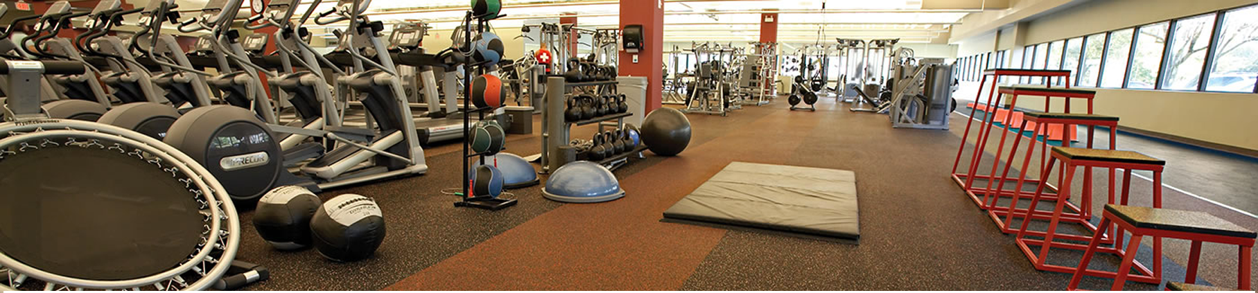 Inside of gym with rolled rubber flooring from Zogics and filled with ellipticals, weights, and lifting machines.