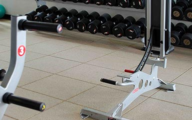 Exercise machines on top of rubber flooring tiles for gyms from Zogics.