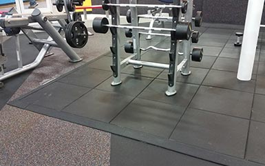 Weightlifting benches and racks on top of rubber flooring tiles for gyms from Zogics.