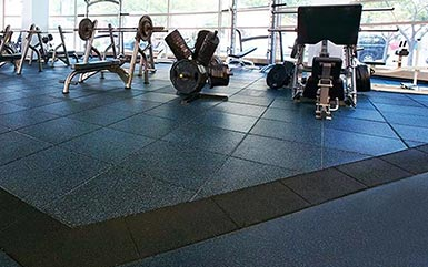 Gym equipment in a fitness center on top of Zogics rubber flooring tiles.