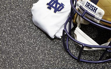 Notre Dame football helmet on top of rolled rubber flooring from Zogics.
