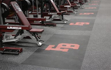 Rolled rubber flooring from Zogics inside gym with row of bench presses.