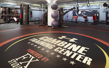 Combine training center gym lined with rolled rubber flooring from Zogics and filled with exercise equipment.