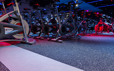 Cycling exercise machines on top of rolled rubber flooring from Zogics.