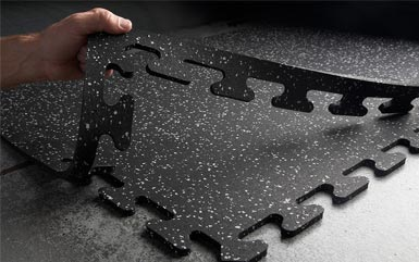 Man pulling up corner segment of black and white speckled interlocking rubber puzzle tiles from Zogics.