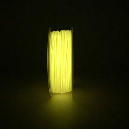A spool of glow in the dark orange pla.