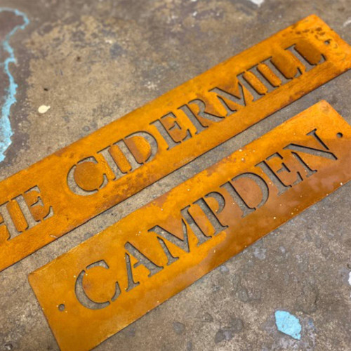 Extra long and narrow house signs from rusty steel. Corten Steel gate signs. Rusty metal gate signs. Lettering cut into a single line.