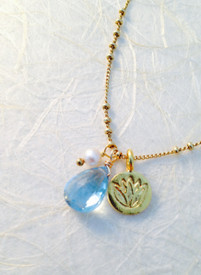 Blue Topaz gold necklace is graced with a lotus charm in 18k vermeil and a freshwater pearl.