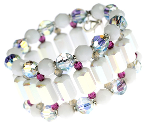 Cuff bracelet surrounds wrist with different colored Swarovski crystals. The Swarovski strung memory wire holds perfect form while displaying crystal colors including antique white, sand, light azure blue, and fushcia.