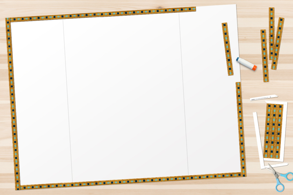 papyrus paper Egyptian borders being glued to the edges of a poster board
