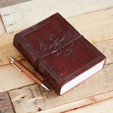 Lifestyle image of Indra leather-bound Winged Dragon Journal, shown on desk with ballpoint pen