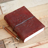 Lifestyle image of Indra leather-bound Mandala journal, shown on table with ballpoint pen