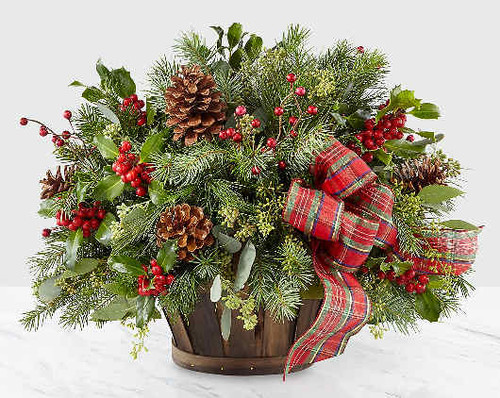 Whether you're welcoming your family home or sharing a gift filled with natural cheer, our Holiday Homecomings Basket is the perfect arrangement to do so. A lush collection of assorted Christmas greens, seeded eucalyptus and holly come together a rustic wooden basket. Accented by a red and green ribbon, pinecone pics and metallic berry pics, this arrangement adds a touch of charm to wherever its placed.