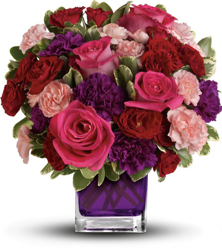 Pure romance. Hot pink roses and dark red spray roses are brightly arranged inside our violet cube.