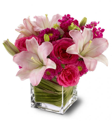 Show impeccable taste when you send this stylish bouquet of hot pink roses, pale pink lilies and mixed blossoms, arranged in a modern glass cube vase. Pretty, posh and perfectly high-class!