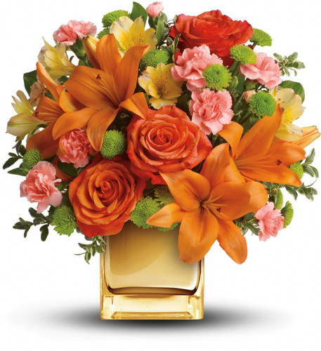 Glow for it! Capture the magic of a tropical sunset with this gorgeously glowing bouquet. Lush lilies and roses in radiant shades of orange and yellow are presented in a Contemporary Cube for a touch of instant glam.