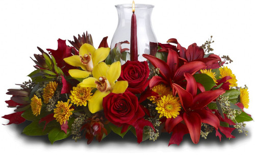 Graceful. Glowing. Gorgeous. This stunning centerpiece will make setting the mood and the Thanksgiving table nothing less than perfect. Fall's most fabulous flowers surround a candle inside hurricane glass. Now that's true class.