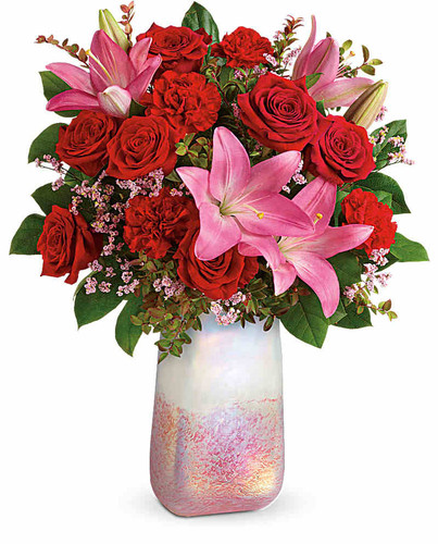 Inspired by the rose quartz gemstone that symbolizes love, this shimmering, hand-blown art glass vase is the perfect backdrop for this romantic pink and red bouquet.  This bouquet features red roses, pink asiatic lilies, red carnations, pink limonium, red huckleberry, and lemon leaf.  Delivered in Teleflora's Pretty In Quartz vase. Orientation: All-Around