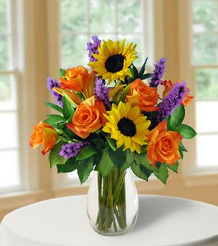 This bouquet is a warm invitation to celebrate the fun of this spectacular season! Our finest orange roses, lilies, sunflowers, purple liatrice and accenting ruskus come together to create bright seasonal hues. This is a gorgeous arrangement of color-kissed blooms that your special recipient will cherish.