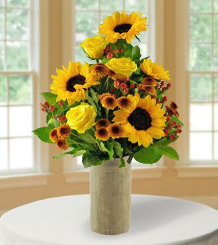 Say hello with our striking arrangement of radiant sunflowers, button poms, roses, hypericum and fresh ruskus greenery. All presented in an included burlap wrapped glass vase, this sunny bouquet is bursting with fall country charm, and will bring a smile to that someone special this harvest season!