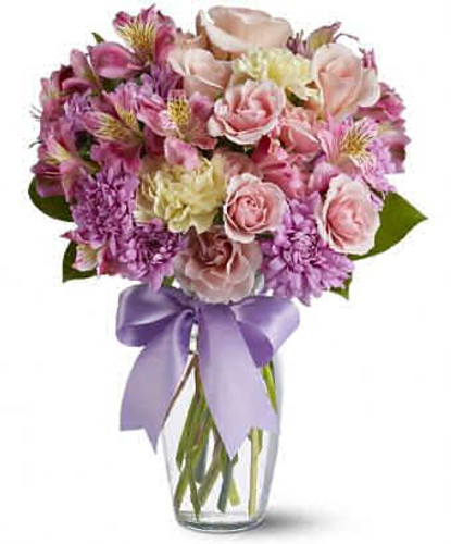 A mix of fresh flowers such as pink spray roses and alstroemeria, yellow carnations and lavender cushion chrysanthemums are delivered in a clear glass vase tied with a lavender ribbon.
