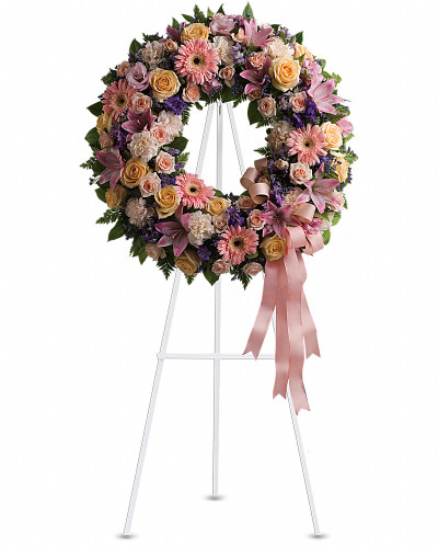 Family and friends will recollect how special their loved one was with this gentle ring of pastel blooms. Highlighted with a pink satin ribbon, it is a lovely reminder of sweet memories and beautiful times shared.  Peach roses, gerberas and carnations, pink asiatic lilies and lisianthus, along with purple limonium and lavender larkspur - accented by greens woven throughout - are presented on an easel-mounted wreath, ideal for a memorial occasion.