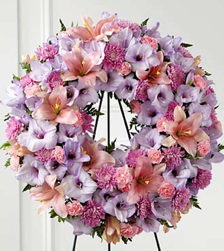 The FTD® Sleep in Peace™ Wreath is a soft expression of sympathy that will bring comfort and offer hope during the final farewell. Lavender gladiolus, pink Asiatic lilies, lavender chrysanthemums, pink mini carnations and lush greens are beautifully arranged in the form of a wreath for a sweet and colorful look. Displayed on a wire easel, this wreath is a lovely way to honor the life of the deceased. Approximately 22-inches in diameter.
