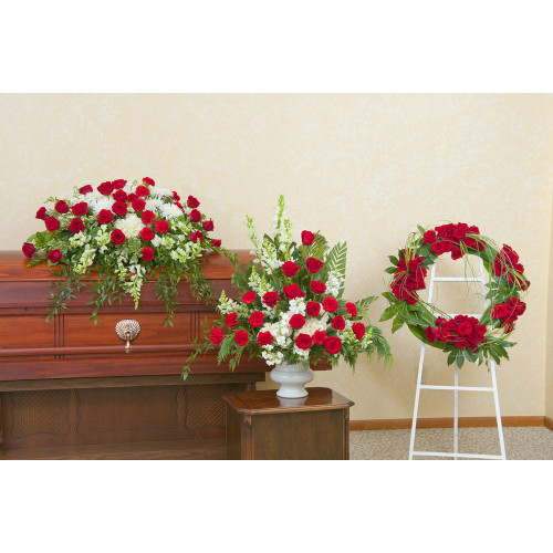 Red and white casket spray, urn and wreath.  Roses, Hydrangea, Gerbera Daisies, Spider Poms and Ruscus make up this complimentary trio.