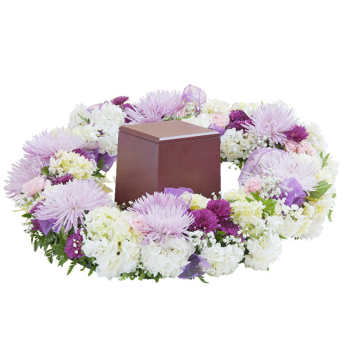 "Soft pastel pink and lavender blooms create a beautiful setting to cradle the urn. Approximately 24"" W by 24"" D"