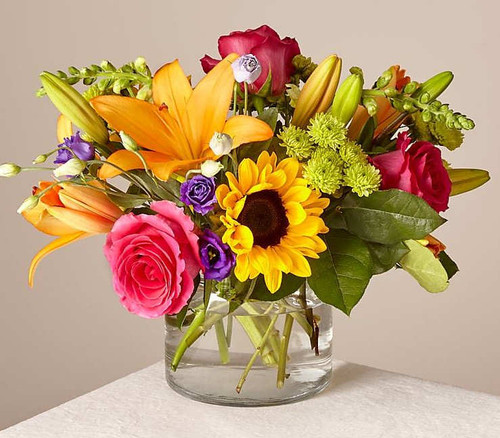 Make this day their best day. Our local florist handcraft a colorful array of flowers in a clear glass vase to create a celebration in bloom. Perfect to give for a special reason or to simply share a smile.