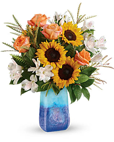This magnificent arrangement of golden sunflowers and orange roses, presented in a hand-blown art glass vase, brings the beauty of an ocean sunset to any occasion.   Light orange roses, white alstroemeria, and medium yellow sunflowers are arranged with grevillea and lemon leaf.