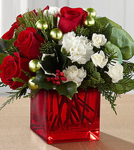 Blossoming with a Christmas charm that evokes memories of holiday seasons long past while nodding towards a sophisticated modern styling, this holiday flower arrangement is ready to spread the joy of the season to your recipient. Rich red roses and white carnations and mini carnations are artistically arranged amongst variegated holly and an assortment of fresh Christmas greens. Accented by matte green glass holiday balls and a sage green wired taffeta ribbon while seated in a red glass cubed vase, this stunning Christmas flower bouquet is ready to create a holiday memory your recipient will never forget.
