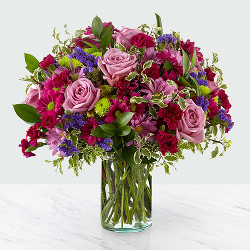 Dazzle your loved ones with stunning violet and green hues set within a glass cylinder vase. A collection of roses, daisies and statice, our Sweet Nothings Bouquet sends sweet sentiment deep within each bloom.