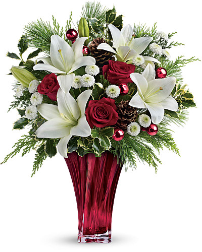 Send them the wonders of winter with beautiful red roses, snow white lilies and fresh winter greens arranged in an elegant and unique glass vase.  Red roses, white asiatic lilies and white button chrysanthemums are accented with fresh flat cedar, variegated holly, white pine, pinecones and red ornament balls.  Delivered in Teleflora's stunning Love's Passion vase or similar High End Vase.