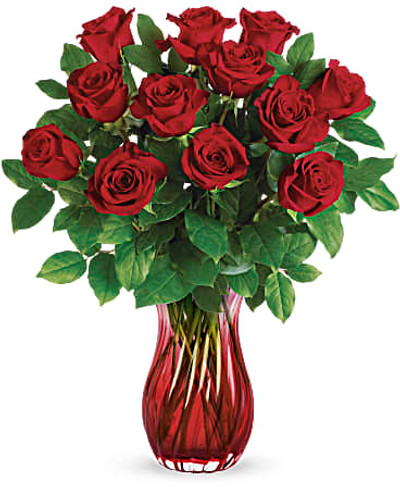 A Valentine's Day classic--with a twist! One dozen ravishing red roses look ultra luxe in this swirling glass vase with ruby red ombre finish.  This classic bouquet includes red roses and lemon leaf. Delivered in Lovely Red Ribbed Glass Vase.