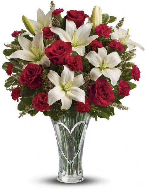 On an Anniversary , or Valentine's Day, send her a gift that's heartfelt - and sure to set her heart aflutter! This dazzling mix of romantic red roses and fragrant, snow white lilies is hand-delivered in a beautiful cut glass vase keepsake she'll enjoy all year long.  Actual vase may vary but will be a High End vase.