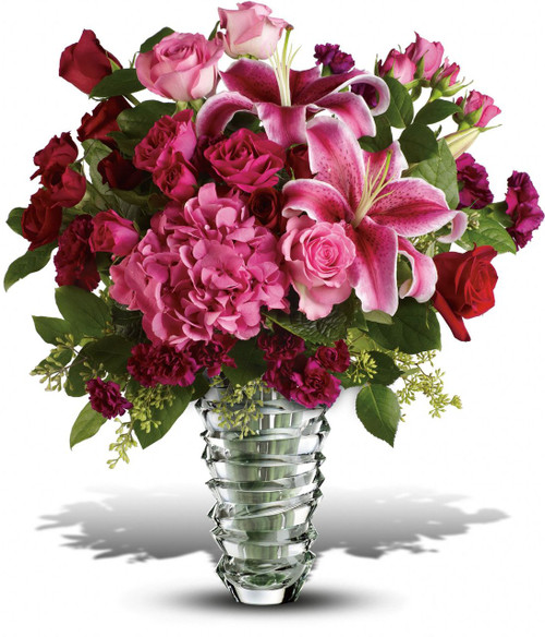 Romantic flowers in a dazzling contemporary glass vase with sculpted rings so vibrant they seem to whirl - a tornado of love. No doubt about it, she'll be swept away by this magnificent gift. Lucky you.