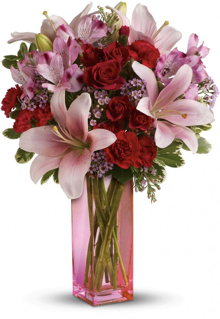 It's a statement she'll always hold close to her heart-lovely lilies and radiant roses that speak to your love and devotion. Arranged lovingly into a pink glass vase, this is a bouquet that brightens any day.