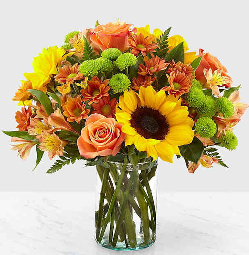 Say hello to autumn with this bouquet filled with bold harvest hues and luscious blooms. Thoughtfully arranged with the freshness of fall in mind, a collection of orange roses, bright sunflowers and orange alstroemeria is set beautifully in a clear glass vase. Whether it's seasonal décor for your home or a gift for a loved one, our Autumn Splendor Bouquet is sure to make any home its placed in feel warm and bright.